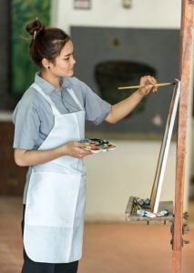 woman painting with an easel