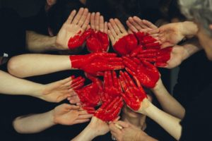 community of hands with a red painted heart in the center